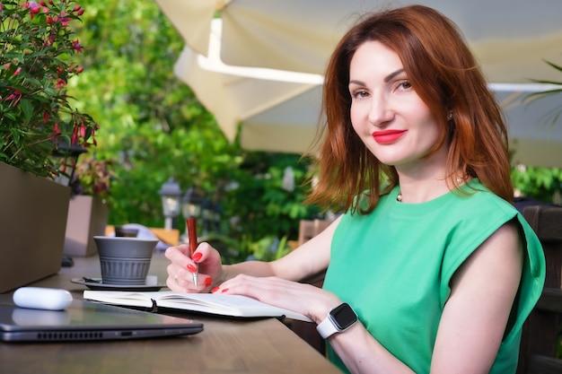 Rothaarige junge frau im eleganten blazer sitzt auf der offenen terrasse des cafés mit laptop, tasse kaffee und macht notizen im notebook. arbeiten außerhalb des büros, freiberufler, vorbereitung auf ein geschäftstreffen