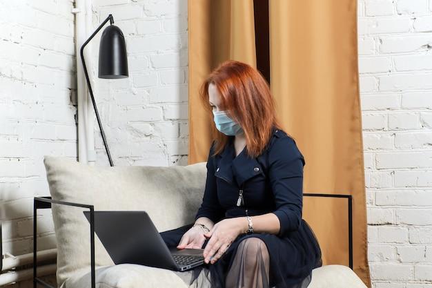 Rothaarige junge frau in der medizinischen maske in der wohnung mit laptop und blick auf bildschirm. konzept remote-arbeit, videokonferenz mit kollegen, online-training