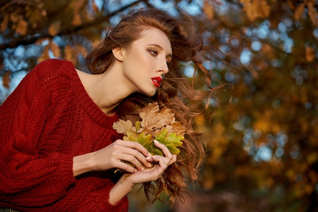 Rothaarige junge frau in einem roten pullover geht in den park. herbstschönheitsporträt einer modischen rothaarigen frau bei sonnenuntergang