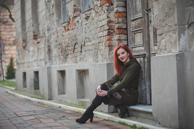 Rothaarige junge frau in einem schönen winterkleid, die am eingang eines alten gebäudes sitzt
