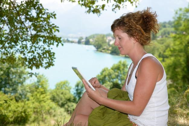 Rothaarige junge frau mit einem digitalen tablett