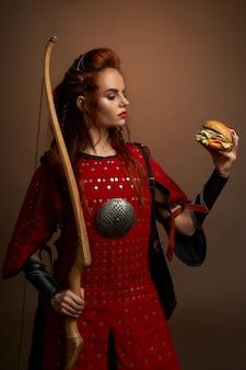 Rothaarige kriegerin mit bogen, die hamburger hält