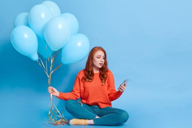 Rothaarige schöne lächelnde kaukasische frau im lässigen pullover und in den jeans mit heliumballons unter verwendung des smartphones auf blauer wand