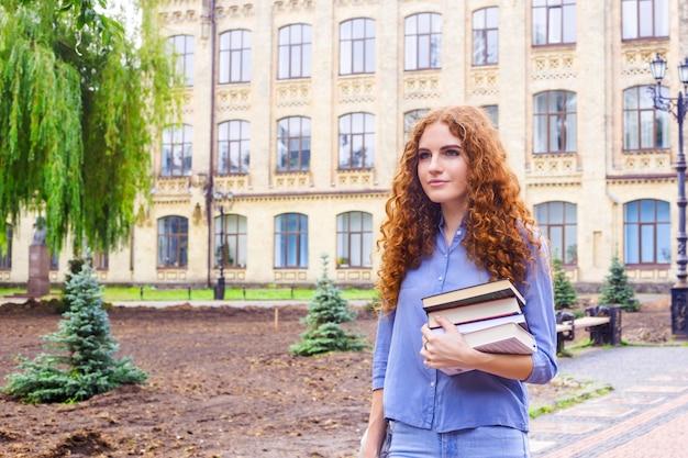 Rothaarige studentin mit einem stapel bücher aus der universitätsbibliothek