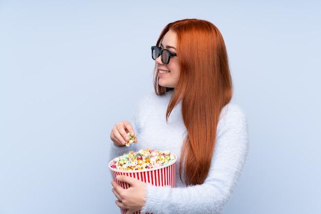 Rothaarige teenager-mädchen über isolierte blaue wand mit 3d-brille und halten einen großen eimer popcorn