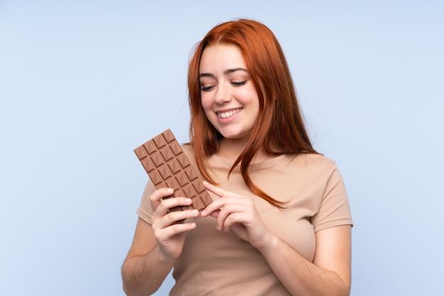 Rothaarige teenagerfrau, die eine schokoladentafel nimmt und glücklich