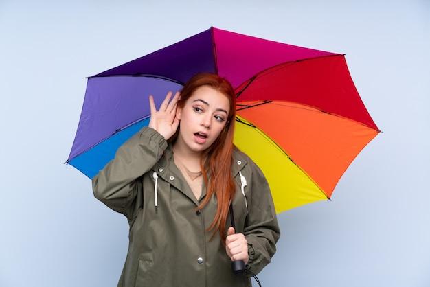 Rothaarige teenagerfrau, die einen regenschirm hält, der etwas hört