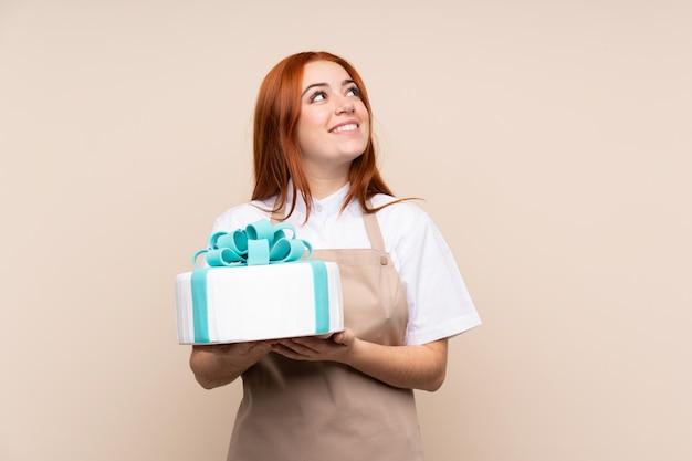 Rothaarige teenagerfrau mit einem großen kuchen, der beim lächeln nach oben schaut