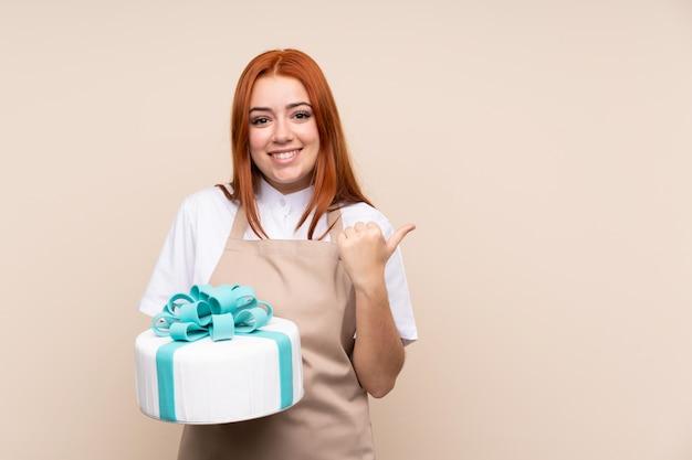 Rothaarige teenagerfrau mit einem großen kuchen, der zur seite zeigt, um ein produkt zu präsentieren