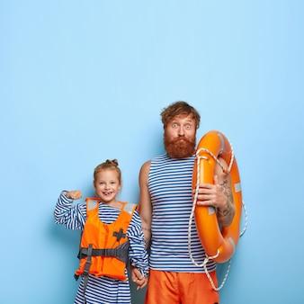 Rothaarige tochter und vater posieren zusammen mit schwimmausrüstung