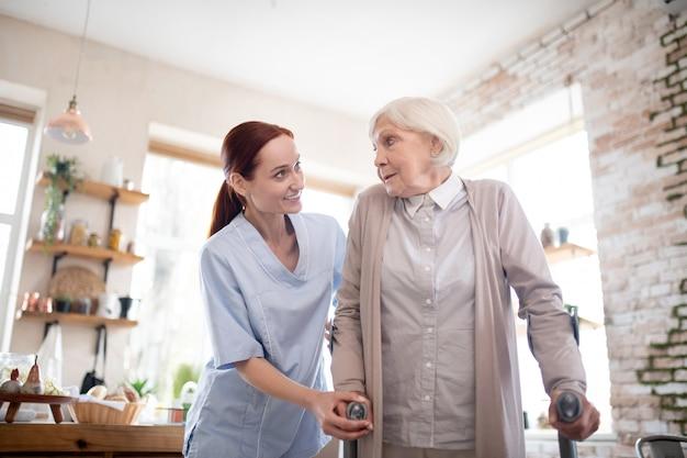 Rothaarige weibliche pflegekraft, die frau mit krücken unterstützt