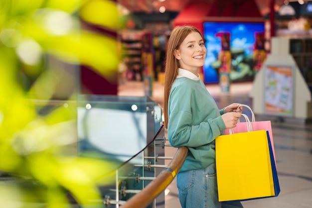 Rothaarigefrau, die bunte einkaufstaschen hält