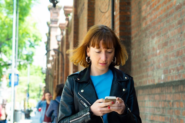 Rothaarigefrau, die mitteilung mit smartphone sendet