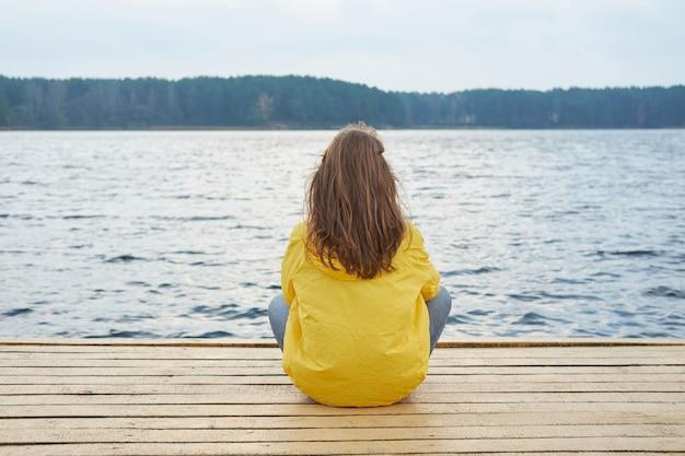 Rothaarigefrau im gelben regenmantel, der auf dem pier des sees sitzt