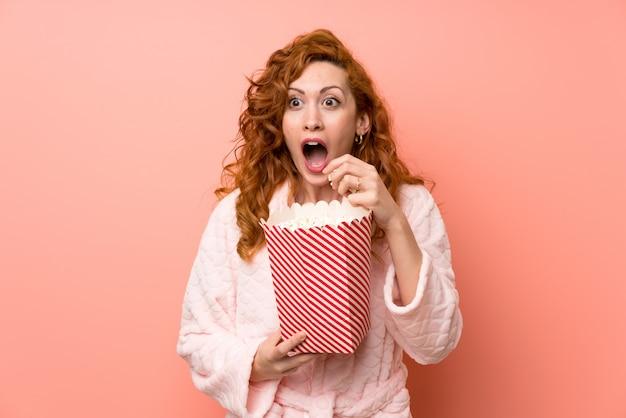 Rothaarigefrau im hausmantel popcorn essend