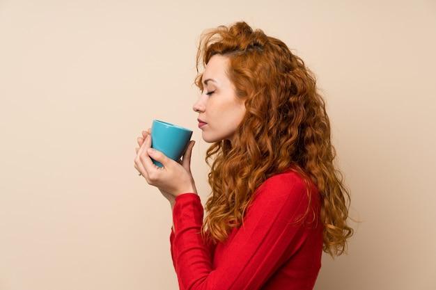Rothaarigefrau mit der rollkragenpullover, die heißen tasse kaffee hält