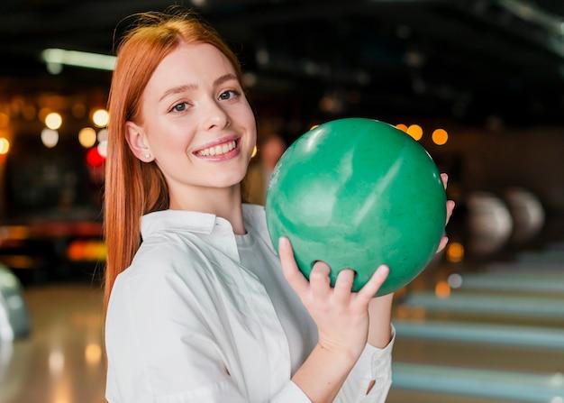 Rothaarigefrau, welche die bowlingkugel hält
