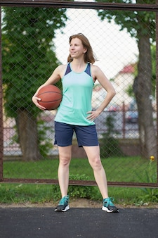 Rothaarigemädchen, das auf dem basketballplatz im freien hält ball und das lächeln steht