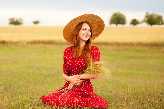 Rothaarigemädchen im roten kleid am weizenfeld