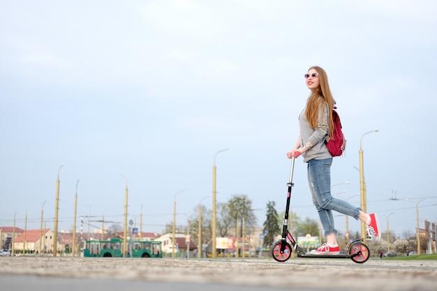 Rothaarigemädchen kleidete im grauen kapuzenpulli, in den blue jeans und in den roten turnschuhen an, die trittroller nahe modernem gebäude reiten