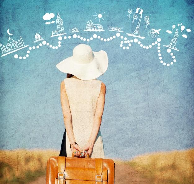 Rothaarigemädchen mit koffer an der landschaftsstraße