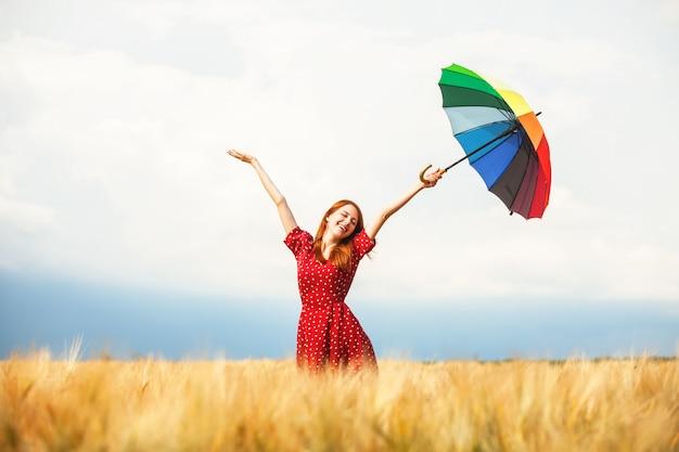 Rothaarigemädchen mit regenschirm am feld
