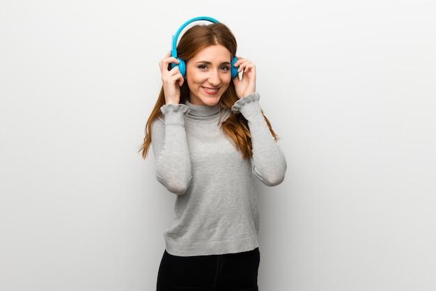 Rothaarigemädchen über weißer wand hörend musik mit kopfhörern