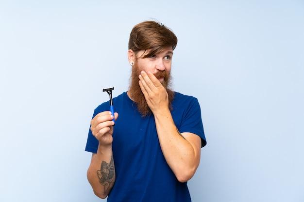 Rothaarigemann, der seinen bart über der lokalisierten blauen wand denkt eine idee rasiert