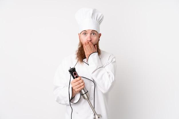 Rothaarigemann, der stabmixer über lokalisierter weißer wand mit überraschungsgesichtsausdruck verwendet