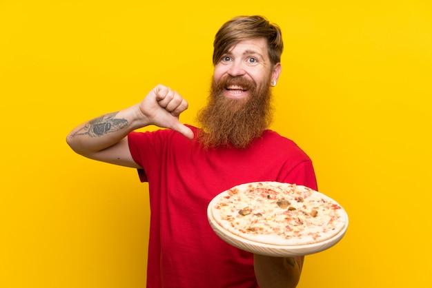 Rothaarigemann mit dem langen bart, der eine pizza über lokalisierter gelber wand stolz und selbstzufrieden hält