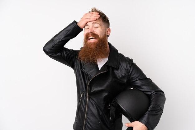 Rothaarigemann mit dem langen bart, der einen motorradsturzhelm über lokalisiertem weißem wandlachen hält