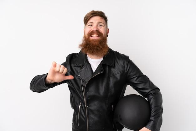 Rothaarigemann mit dem langen bart, der einen motorradsturzhelm über lokalisierter weißer wand stolz und selbstzufrieden hält