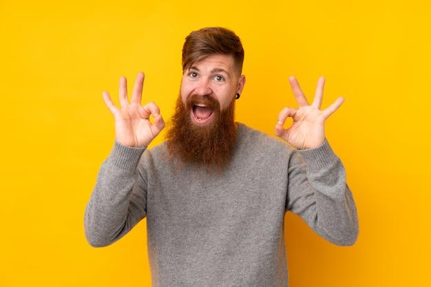 Rothaarigemann mit langem bart über der lokalisierten gelben wand, die ein okayzeichen mit den fingern zeigt
