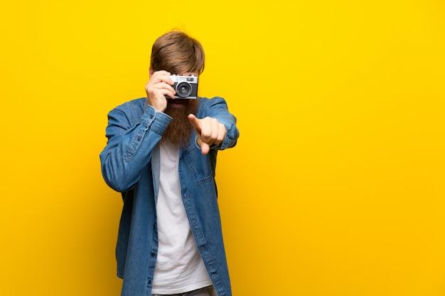 Rothaarigemann mit langem bart über der lokalisierten gelben wand, die eine kamera hält