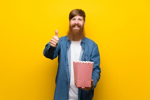 Rothaarigemann mit langem bart über der lokalisierten gelben wand, die eine schüssel popcorn hält
