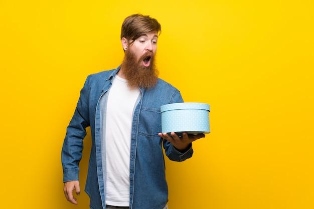 Rothaarigemann mit langem bart über der lokalisierten gelben wand, die geschenkbox hält
