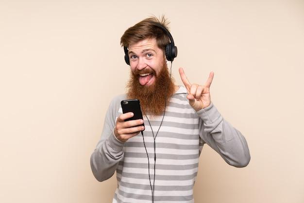 Rothaarigemann mit langem bart über lokalisiertem hintergrund unter verwendung des mobiles mit kopfhörern und dem gesang