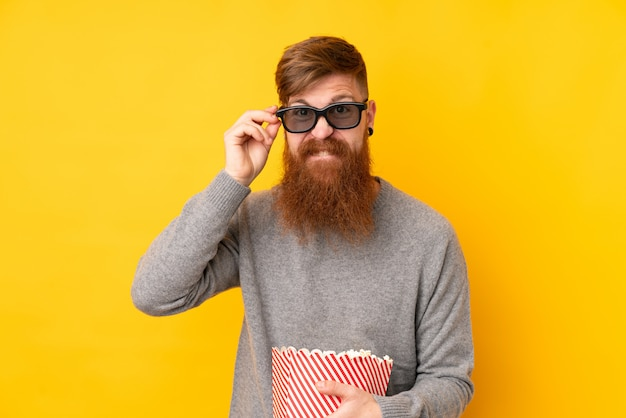 Rothaarigemann mit langem bart über lokalisierter gelber wand mit gläsern 3d und dem halten eines großen eimers popcorns