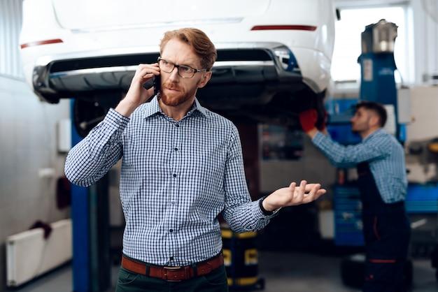 Rothaariger autobesitzer, der am telefon spricht.