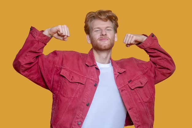 Rothaariger bärtiger junger mann in der roten jacke, die muskeln zeigt
