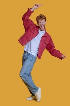 Rothaariger bärtiger junger mann in roter jacke, der aufgeregt ist