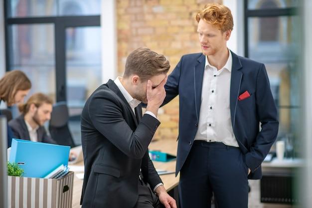 Rothaariger ernsthafter mann im anzug, der einen unglücklichen kollegen unterstützt, der auf tisch in einem büro sitzt