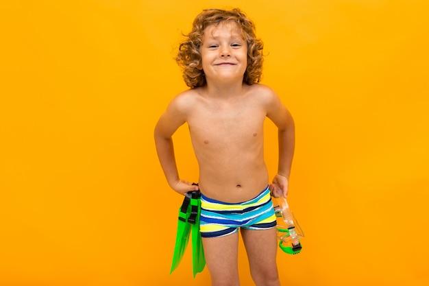 Rothaariger gelockter junge hält schwimmflossen über gelbem hintergrund