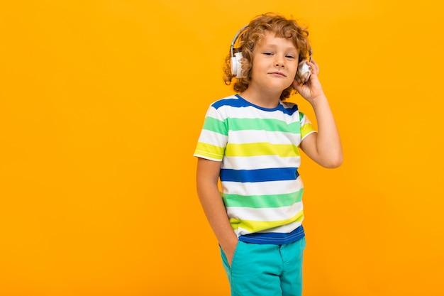 Rothaariger gelockter junge hört musik in den großen kopfhörern auf einem gelben hintergrund