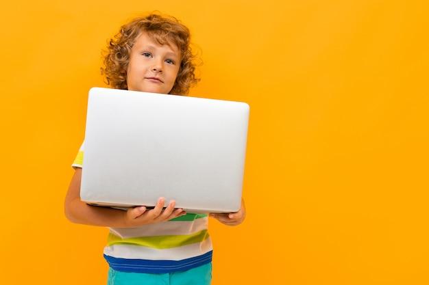Rothaariger gelockter junge mit einem laptop auf einem gelben hintergrund