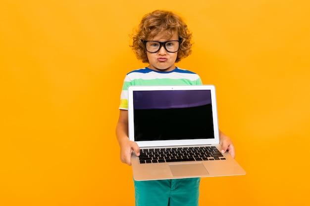 Rothaariger gelockter junge mit gläsern zeigt einen laptopschirm auf einem gelben hintergrund
