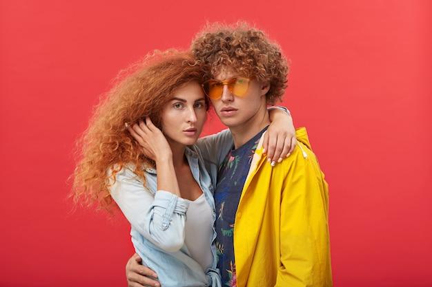 Rothaariger hipster in schattierungen und gelbem regenmantel, der seine schöne freundin festhält