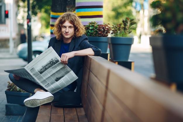 Rothaariger hipster-mann, der auf bank mit zeitung sitzt