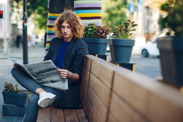 Rothaariger hipster-mann, der auf bank sitzt und zeitung liest