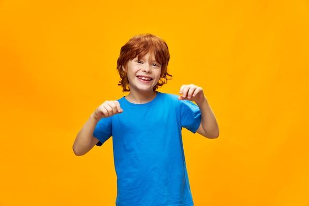 Rothaariger junge in einem blauen t-shirt posiert